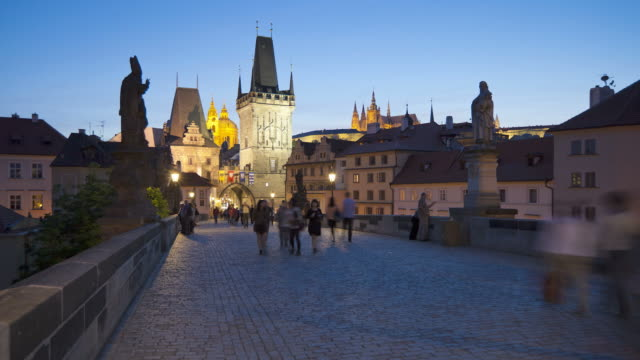 pedestrians move across the illuminated charles bridge at night. - charles bridge stock videos and b-roll footage