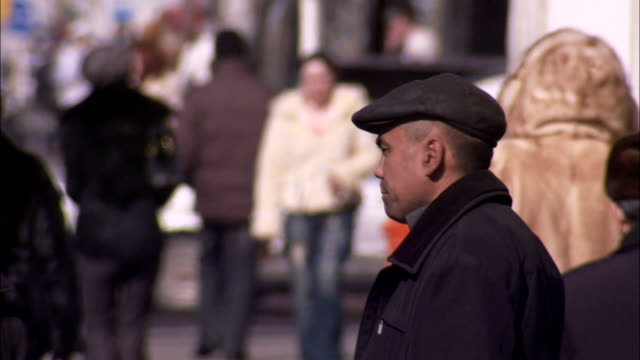 pedestrians move along a busy street. available in hd. - cappotto invernale video stock e b–roll