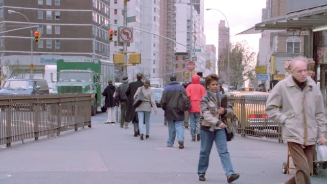 vídeos y material grabado en eventos de stock de pedestrians move along a fenced sidewalk in inner-city new york city. - toma en travelling