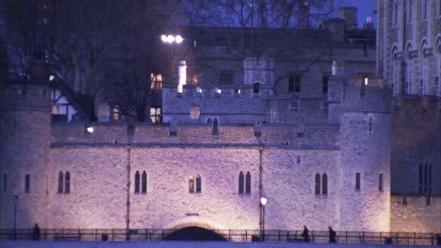 pedestrians move along a path outside the tower of london. - tower of london stock videos and b-roll footage
