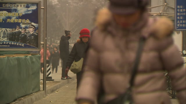 pedestrians on a city street in beijing, china. - smog stock videos & royalty-free footage