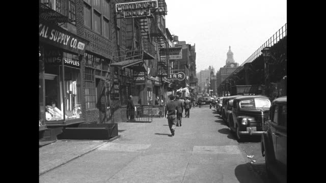 Pedestrians on broad sidewalk in the Bowery with The White House Rooms for Men sign on facade of building / Note exact year not known
