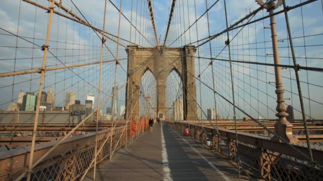 Pedestrians on Brooklyn Bridge on sunny spring day with Manhattan skyline.