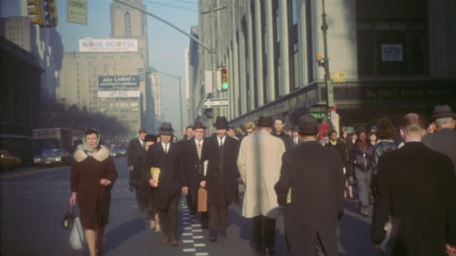 vídeos de stock e filmes b-roll de 1959 ms pedestrians on busy manhattan sidewalk during winter / new york city, new york - 1950 1959