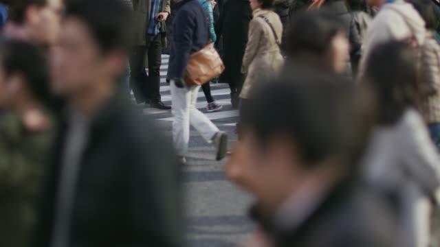 slo mo, ls pedestrians on shibuya scramblewalk / tokyo, japan - 混雑した点の映像素材/bロール