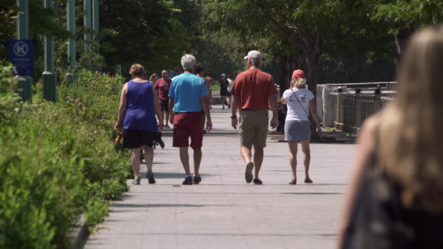 Pedestrians on sidewalk during hot summer day.
