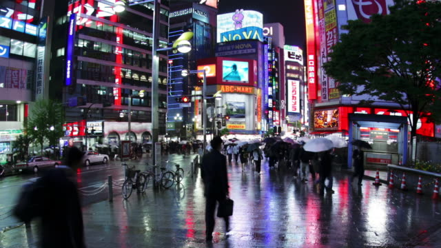 pedestrians on the sidewalk in east shinjuku carrying umbrellas / tokyo, japan - insegna commerciale video stock e b–roll