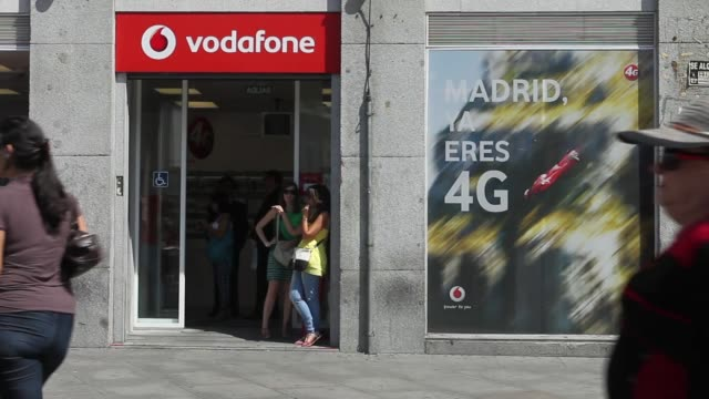 pedestrians pass a closed down vodafone store operated by vodafone group plc as graffiti art sits alongside the company's logo in madrid spain on... - plc stock videos & royalty-free footage