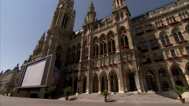 pedestrians pass a large screen positioned outside vienna rathaus. available in hd. - rathaus stock-videos und b-roll-filmmaterial