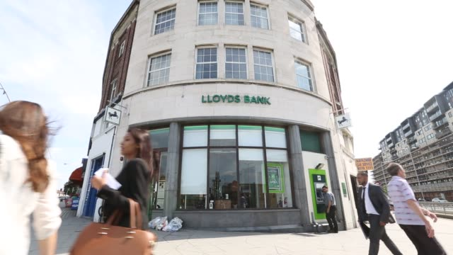 pedestrians pass a lloyds bank branch a unit of lloyds banking group plc in london uk the lloyds prancing horse logo sits on a sign outside the... - banking sign stock videos & royalty-free footage