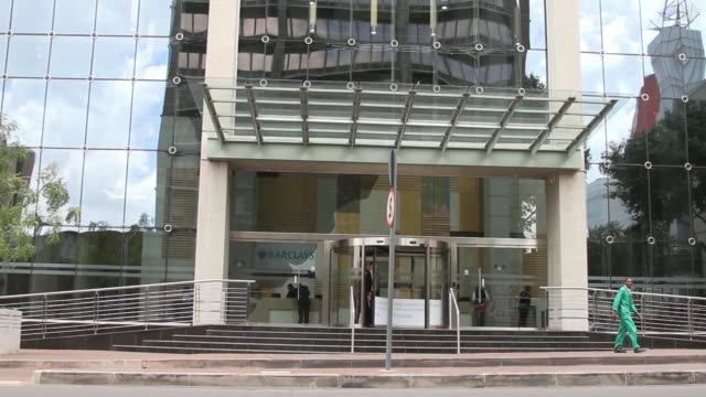 stockvideo's en b-roll-footage met pedestrians pass a logo outside the headquarters of absa bank ltd operated by barclays plc in johannesburg south africa on thursday dec 12 visitors... - gauteng provincie