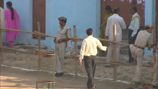 Pedestrians pass a policeman who leans against a split-rail fence in India.