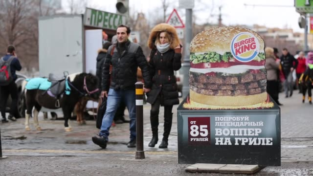 stockvideo's en b-roll-footage met pedestrians pass a street advertisement outside a burger king fast food restaurant in moscow customers enter a burger king fast food restaurant in... - street name sign