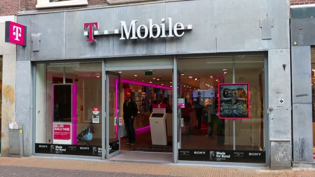 vídeos y material grabado en eventos de stock de pedestrians pass a tmobile store operated by deutsche telekom ag in utrecht netherlands on friday oct 23 smartphone devices sit on display inside a... - t mobile