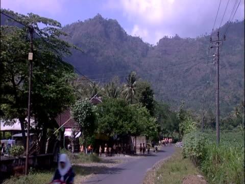 stockvideo's en b-roll-footage met pedestrians pass along road beside mountains. - agrarisch beroep