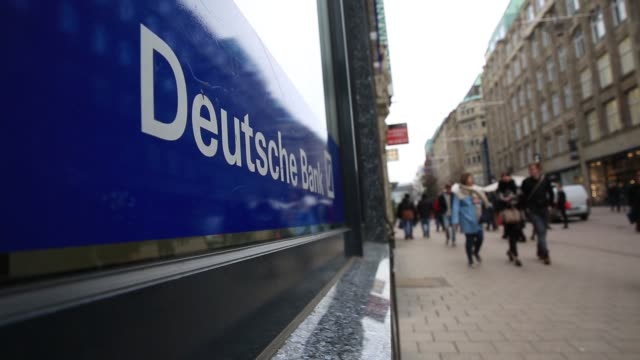 pedestrians pass by a branch of deutsche bank ag in hamburg germany on saturday feb 13 a flag displaying the deutsche bank ag logo flies above a... - deutsche bank stock videos & royalty-free footage