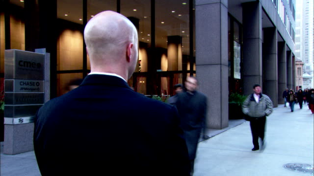 vidéos et rushes de pedestrians pass by a businessman standing in the middle of a sidewalk. available in hd. - invisible