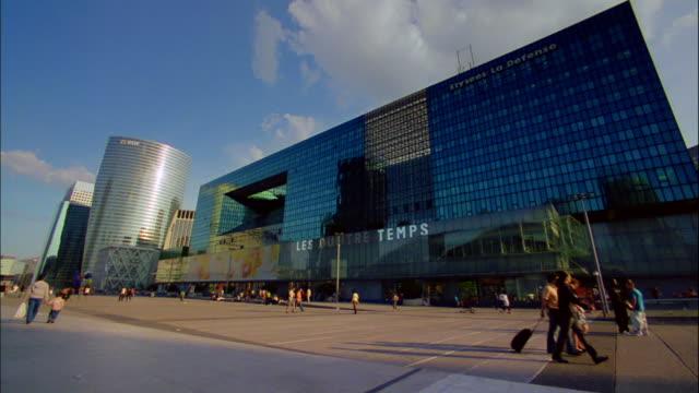 pedestrians pass by a mirrored building. - fensterfront stock-videos und b-roll-filmmaterial