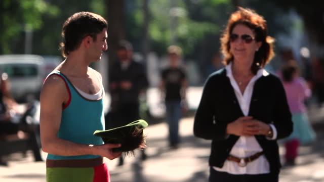 pedestrians pass by a street performer on rothschild boulevard in tel aviv, israel. - tel aviv stock-videos und b-roll-filmmaterial