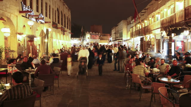 pedestrians pass by patrons sitting at tables outside cafes in souq waqif. - doha stock videos & royalty-free footage