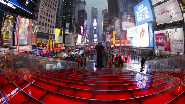 pedestrians pass by red bleachers set up in the middle of times square. - large scale screen stock videos & royalty-free footage
