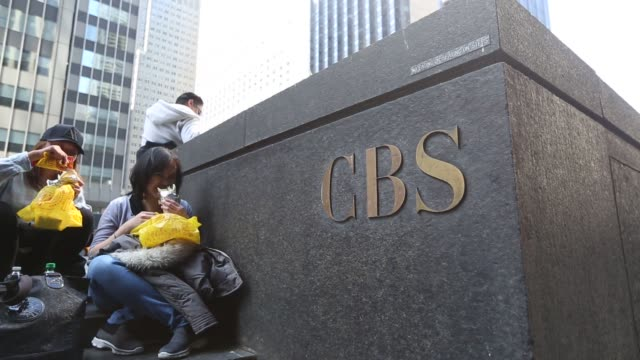 pedestrians pass cbs corp. headquarters in new york, u.s., on saturday april 30, 2016. shots: pans and tilts of cbs logo in garden, cbs sigange on... - headquarters stock videos & royalty-free footage