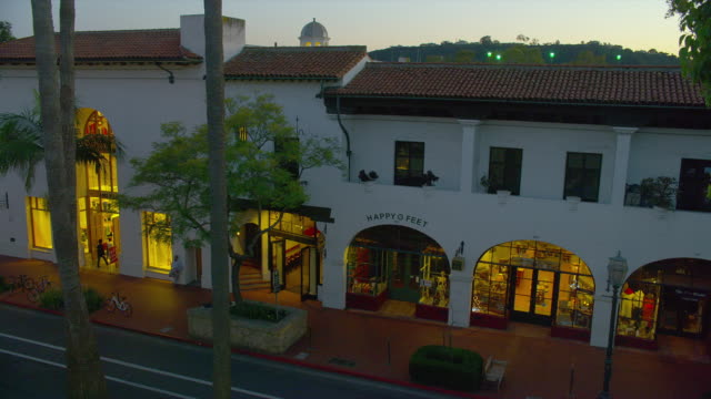 high angle wide pan pedestrians pass happy feet shoe repair and other shops to traffic and pedestrians at intersection of state and canon perdido streets in downtown santa barbara, california at sunset - pavement stock videos & royalty-free footage