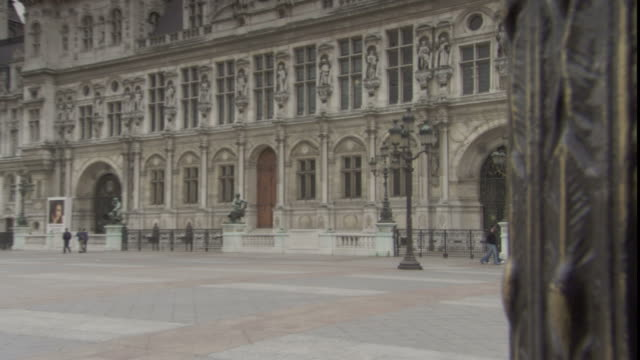 pedestrians pass hotel de ville in paris. - hotel de ville paris stock videos & royalty-free footage