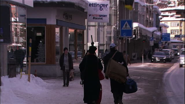 Pedestrians pass hotels and shops in Davos, Switzerland.