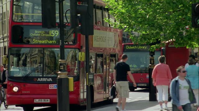 Pedestrians pass in front of a double decker bus.