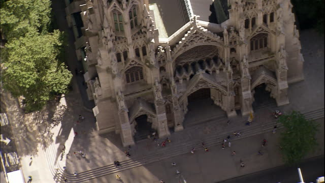 pedestrians pass in front of  st. patrick's cathedral in midtown manhattan. - cathedral stock videos & royalty-free footage