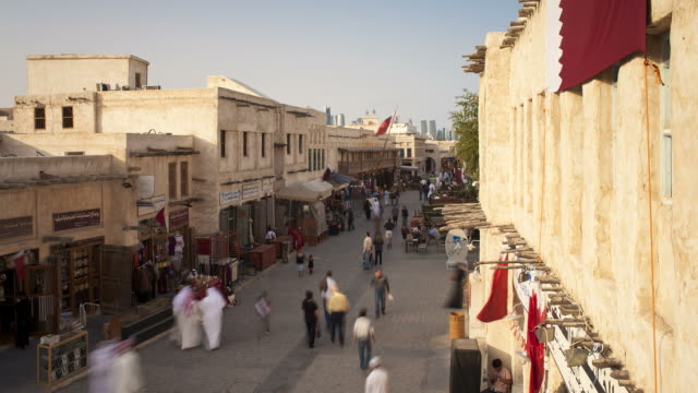 pedestrians pass mud-rendered shops in souq waqif. - qatar stock videos & royalty-free footage