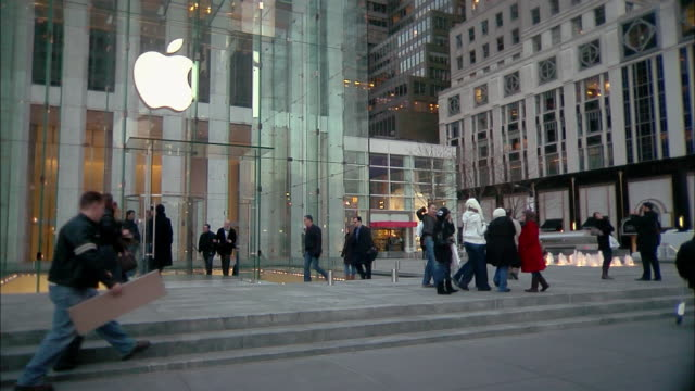 pedestrians pass the apple store on 5th avenue. - apple store stock videos & royalty-free footage