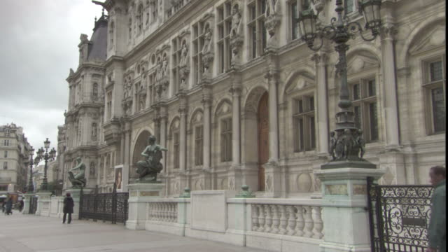 pedestrians pass the arched facade of the hotel de ville in paris. - hotel de ville paris stock videos & royalty-free footage