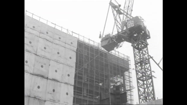 pedestrians pass the construction site of shinjuku station west gate in tokyo. - showa period stock videos & royalty-free footage