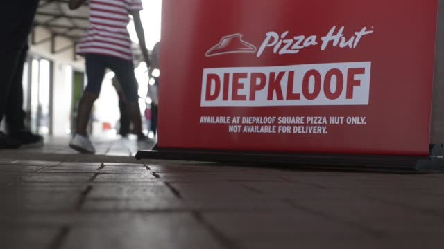 pedestrians pass the entrance to a pizza hut store operated by yum brands inc in the soweto district of johannesburg south africa on saturday feb 14... - soweto stock videos and b-roll footage