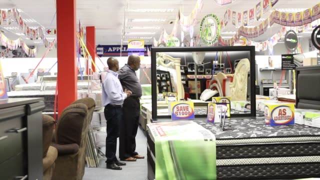 Pedestrians pass the entrance to an OK Furniture store operated by Shoprite Holdings Ltd in Pretoria South Africa on Monday Sept 15 2014 An employee...