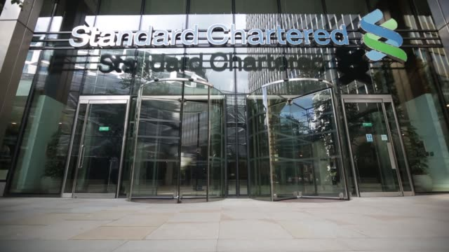 pedestrians pass the entrance to standard chartered plc's headquarters in london uk on monday aug 12th general views standard chartered plc signage... - plc stock videos & royalty-free footage