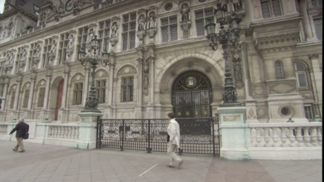 pedestrians pass the hotel de ville in paris. - hotel de ville paris stock videos & royalty-free footage