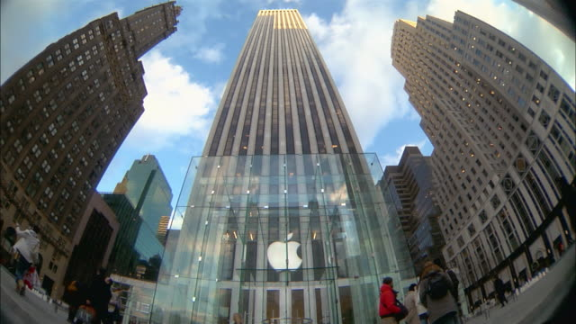 pedestrians pass the hotel sherry-netherland, the apple store, the general motors building and bergdorf goodman. - apple store stock videos & royalty-free footage