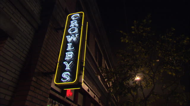 Pedestrians pass under a neon sign for Crowley's sports bar.