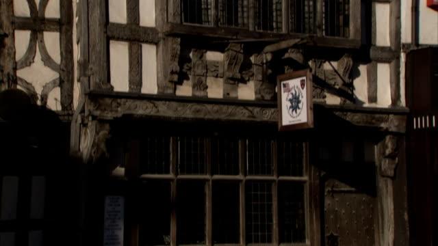 vídeos de stock e filmes b-roll de pedestrians pass under a sign hanging outside a tudor building, stratford upon avon. available in hd. - tudor