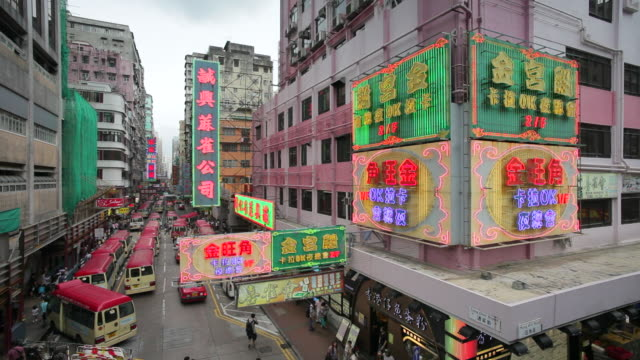 vidéos et rushes de pedestrians pass under bright neon signs above a street in mong kok. - mong kok