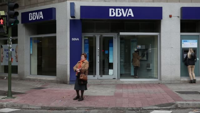 vídeos y material grabado en eventos de stock de pedestrians passa branch of bbva in madrid, spain on wednesday, november 12 a woman withdraws money from a cash machine inside the branch, bbva sign... - rama parte de planta