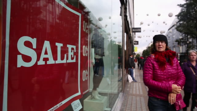 pedestrians passing a shop window with a sale sign on oxford street on october 19, 2016 in london, england. inflation rose to 1.0% in september up... - oxford street stock-videos und b-roll-filmmaterial