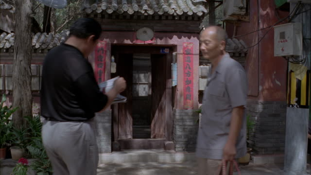 stockvideo's en b-roll-footage met pedestrians passing an entrance to a traditional chinese home. - brievenbus huis
