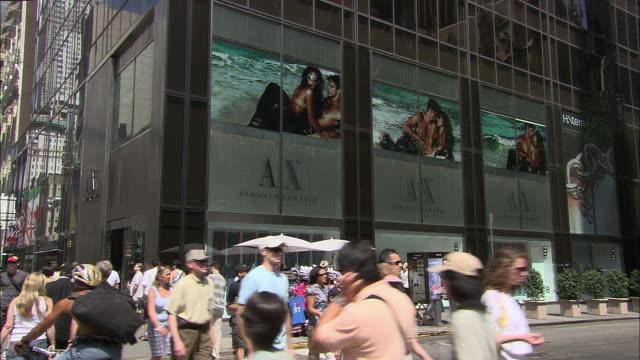 vídeos de stock, filmes e b-roll de ms, pedestrians passing by armani exchange window displays, fifth avenue, new york city, new york, usa - giorgio armani marca de moda