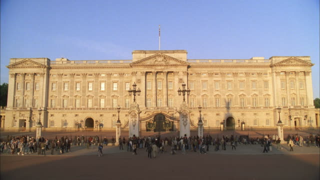 vídeos de stock, filmes e b-roll de la pedestrians passing the east front of buckingham palace / london, england, united kingdom - palácio de buckingham