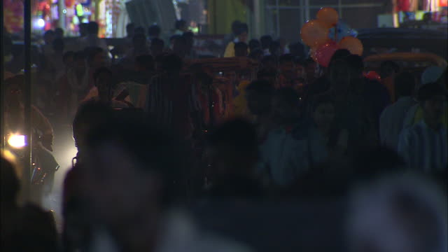 pedestrians, pedicabs and motorcycles crowd a busy street in india. - fahrradtaxi stock-videos und b-roll-filmmaterial