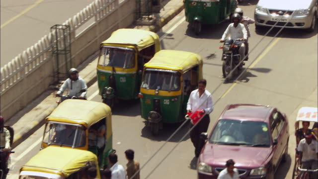 pedestrians, rickshaws and taxis crowd a busy street in new delhi, india. available in hd. - risciò video stock e b–roll